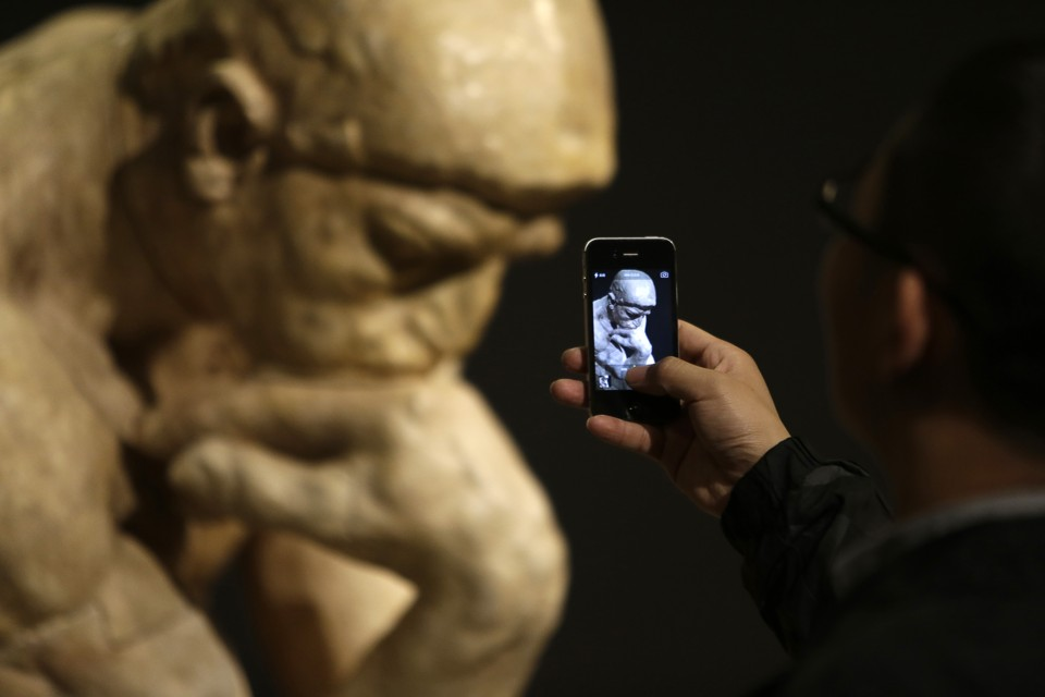"A visitor takes a picture of the sculpture ""The Thinker"" by French artist Auguste Rodin at the National Museum of China in Beijing November 28, 2014. A total of 140 original works created by Rodin, a 19th century sculptor, were on display from Thursday, including The Thinker, The Age of Bronze, Monument to Balzac and other representative works, in Beijing in honour of the 50th anniversary of the establishment of diplomatic relations between China and France, local media reported. REUTERS/Jason Lee   (CHINA - Tags: POLITICS ENTERTAINMENT) - RTR4FWVV"